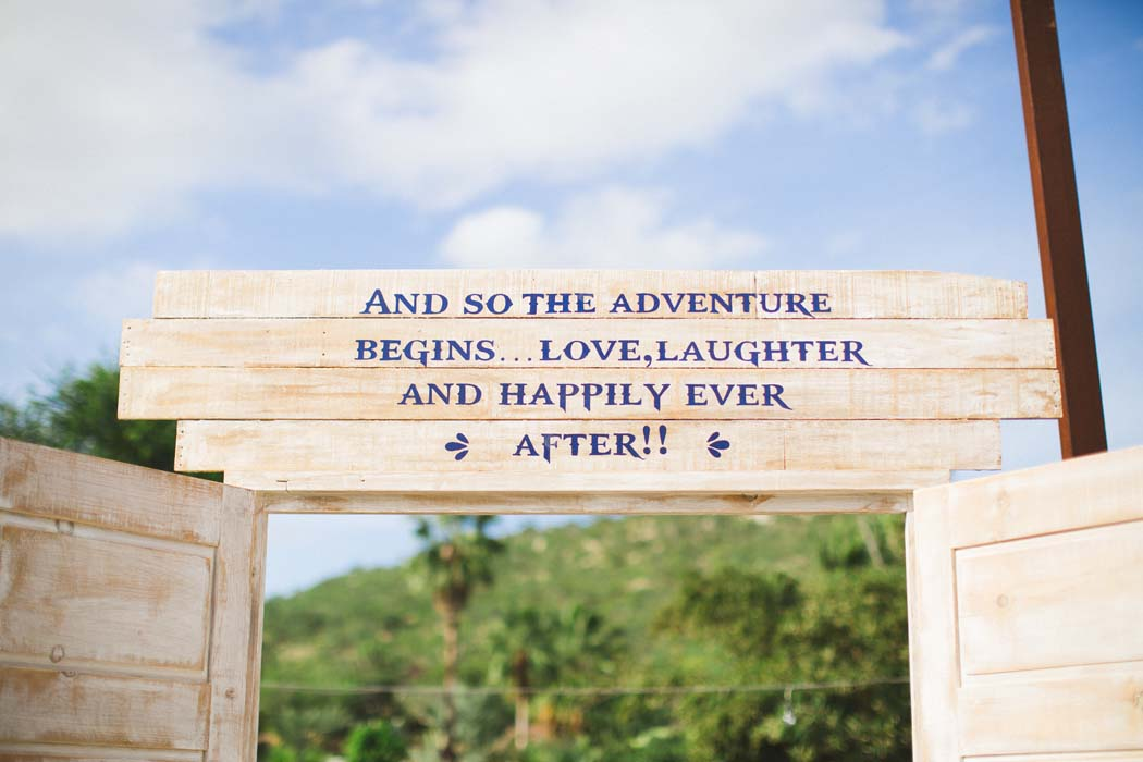 Sign above the entrance in blue lettering, made of wood, for Sarah and Justice's cabo wedding. - Sarah and Justice wedding pic 1