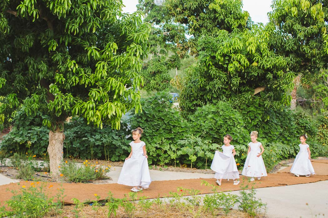 Photo of a group of flower girls walking through a garden in all white dresses at a Cabo wedding. - Sarah and Justice wedding pic8
