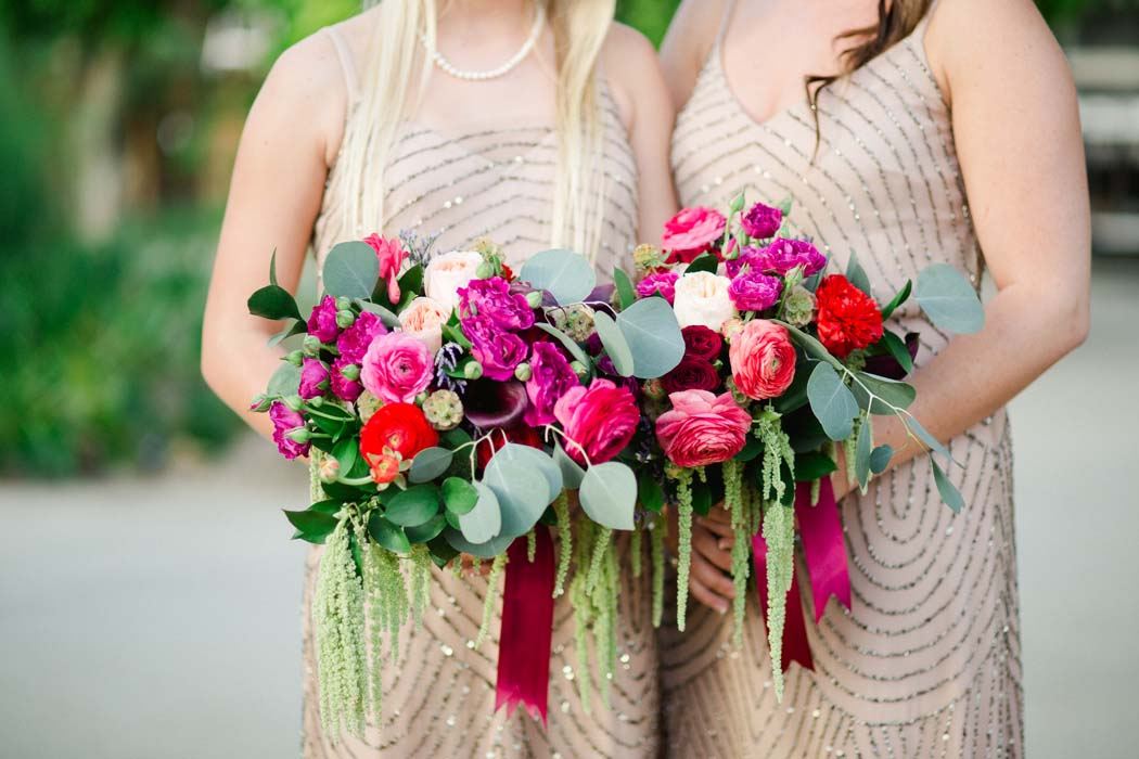Photo of two bridesmaids holding red rose bouquets at Sarah and Justice's cabo wedding. - Sarah and Justice wedding pic4